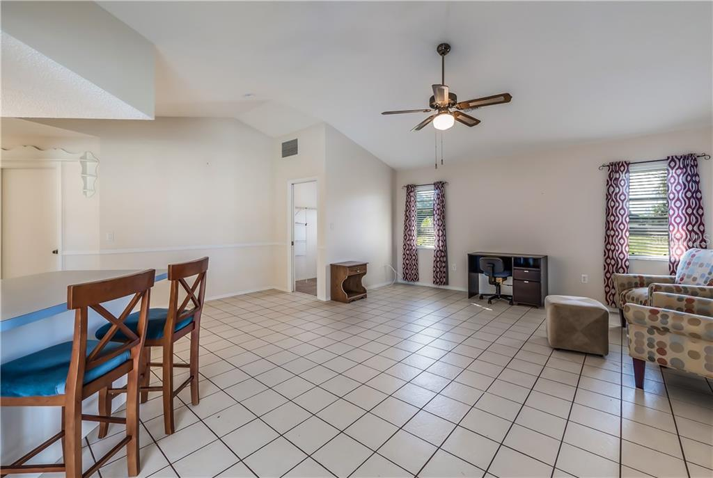 Large family room with breakfast bar at kitchen counter. - Single Family Home for sale at 11010 Deerwood Ave, Englewood, FL 34224 - MLS Number is D5921766