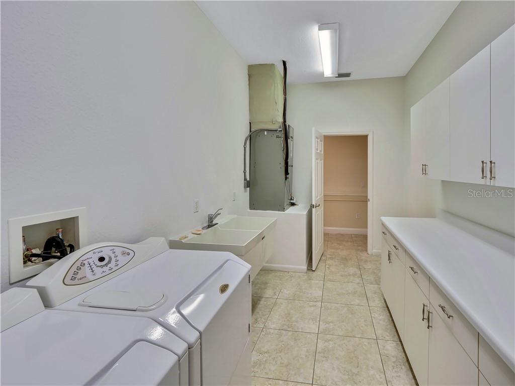 Laundry room, double laundry sinks, long folding counter, storage and half bath off of it. - Single Family Home for sale at 13283 Eisenhower Dr, Port Charlotte, FL 33953 - MLS Number is D6107998