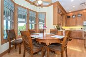 Casual dining area with custom window treatments and beautiful wood framed windows. - Single Family Home for sale at 550 S Oxford Dr, Englewood, FL 34223 - MLS Number is D6111512