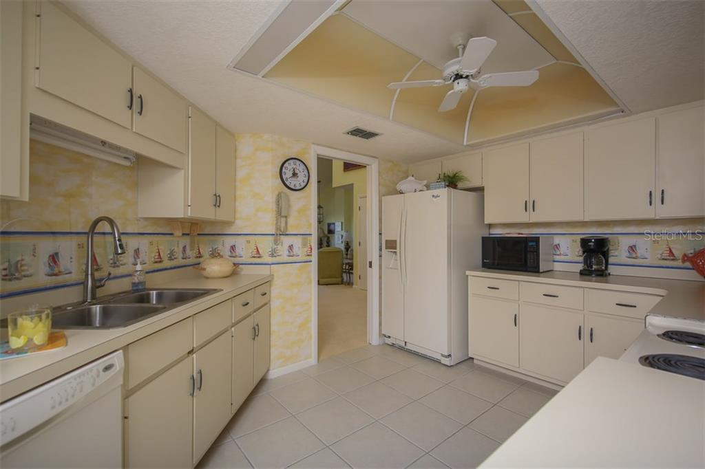 Charming kitchen is between the living room and family room with tile flooring - Condo for sale at 1765 Jamaica Way #302, Punta Gorda, FL 33950 - MLS Number is C7234643