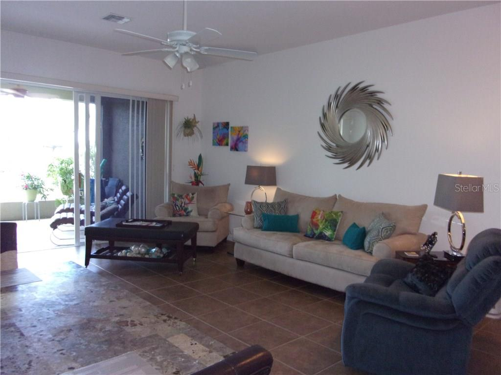 Living Area with 9' Ceilings and Oversize Sliding Doors Leading to the Lanai - Villa for sale at 1912 Knights Bridge Trl, Port Charlotte, FL 33980 - MLS Number is C7239595