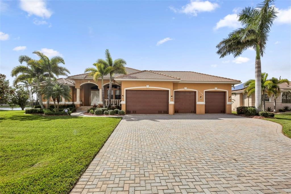 Expansive paver drive leads you to this 3BR/2.5BA home that boasts an awesome 4 car garage! - Single Family Home for sale at 17208 Barcrest Ln, Punta Gorda, FL 33955 - MLS Number is C7245458