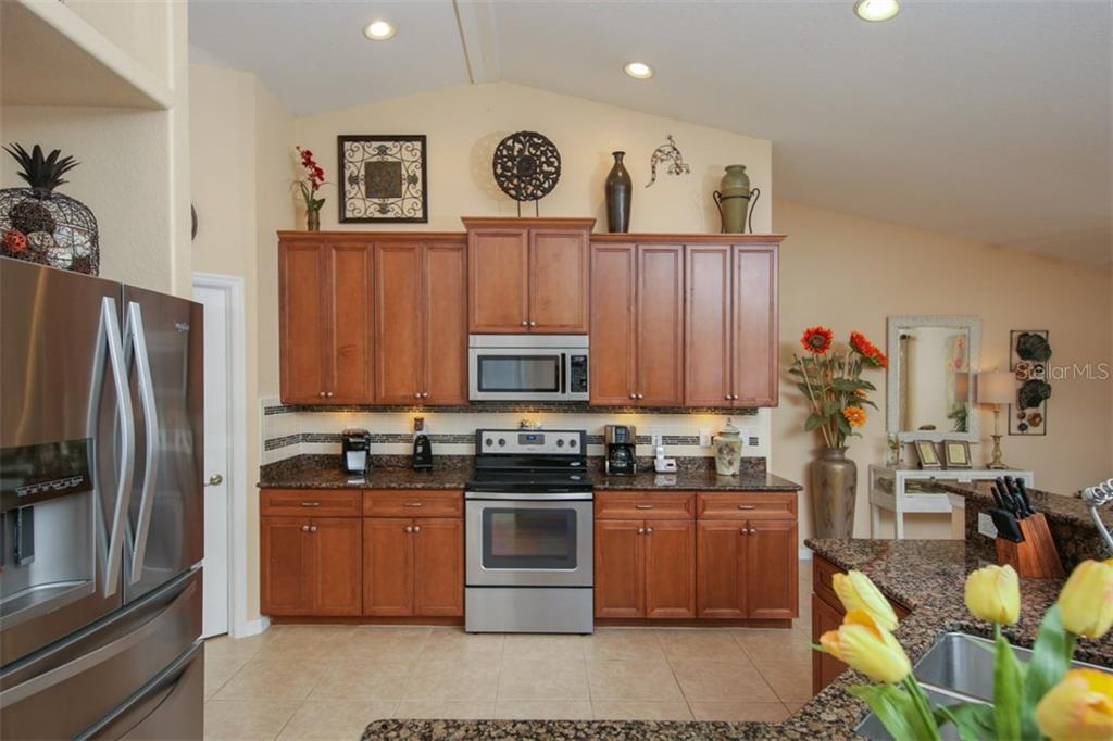 Tiled backsplash and stainless steel appliances compliment this gourmet chef's dream! - Single Family Home for sale at 220 Broadmoor Ln, Rotonda West, FL 33947 - MLS Number is C7248036
