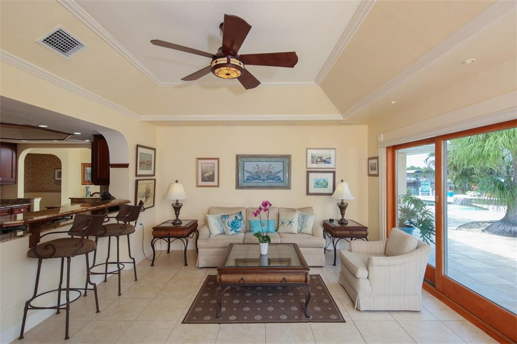 Florida Room has tile flooring and enjoys tropical views of the outdoors - Single Family Home for sale at 158 Morgan Ln Se, Port Charlotte, FL 33952 - MLS Number is C7400633