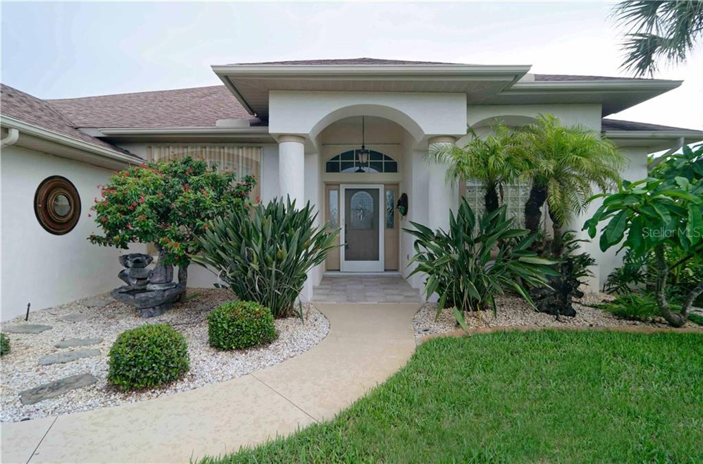 Close-up view of the front entry.  Notice the beautiful landscaping and fountain. - Single Family Home for sale at 9199 Key West St, Port Charlotte, FL 33981 - MLS Number is C7403206
