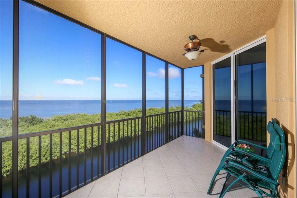 This right view provides both Charlotte Harbor and channel views where you can enjoy a daily parade of vessels coming and going from the north marina basin.  Sliding glass doors pictured here open to the master suite. - Condo for sale at 3329 Sunset Key Cir #503, Punta Gorda, FL 33955 - MLS Number is C7406727