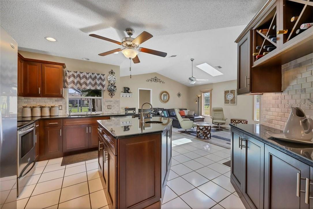 view of kitchen and family room  from dining area - Single Family Home for sale at 116 Mariner Ln, Rotonda West, FL 33947 - MLS Number is C7441260