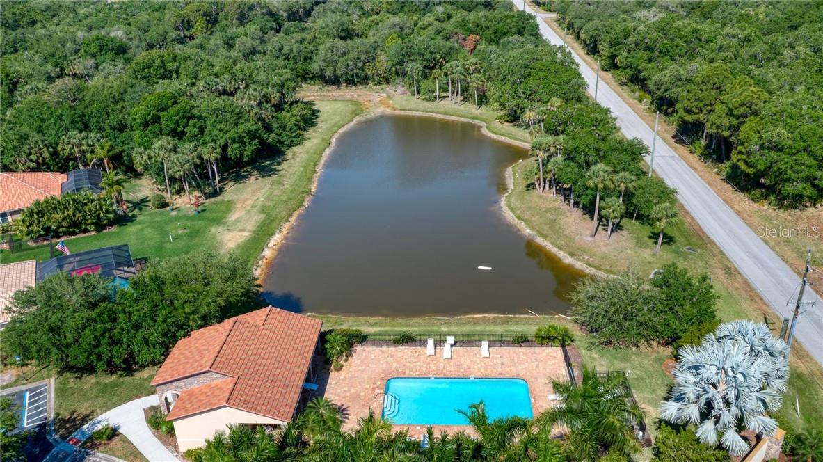 The pool house, pool, and view of a lake offers a relaxed environment to enjoy the Florida lifestyle. - Single Family Home for sale at 2082 Apian Way, Port Charlotte, FL 33953 - MLS Number is C7441465