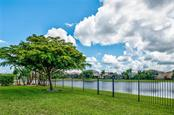 A fenced yard and a view of the Lake - Single Family Home for sale at 24123 Riverfront Dr, Port Charlotte, FL 33980 - MLS Number is C7402813