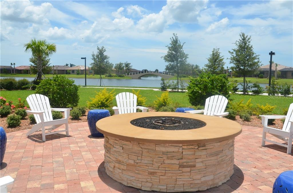 Community fire pit for residents to gather and enjoy. Note the walking paths that are consistent throughout the large neighborhood with bridges over the chains of water. Bike racks are located near town center for residents convenience. - Single Family Home for sale at 13328 Coluccio St, Venice, FL 34293 - MLS Number is A4160649