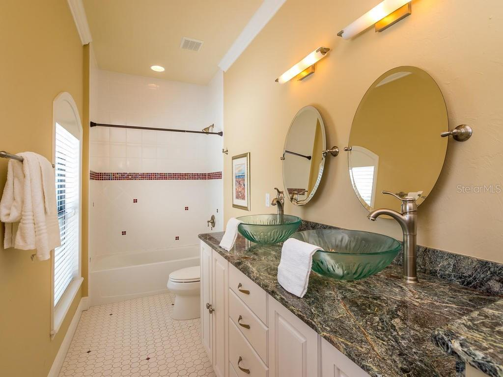 Beautiful guest bathroom upstairs with dual glass bowl sinks and tub-shower combo! - Single Family Home for sale at 1884 Grove St, Sarasota, FL 34239 - MLS Number is A4189365
