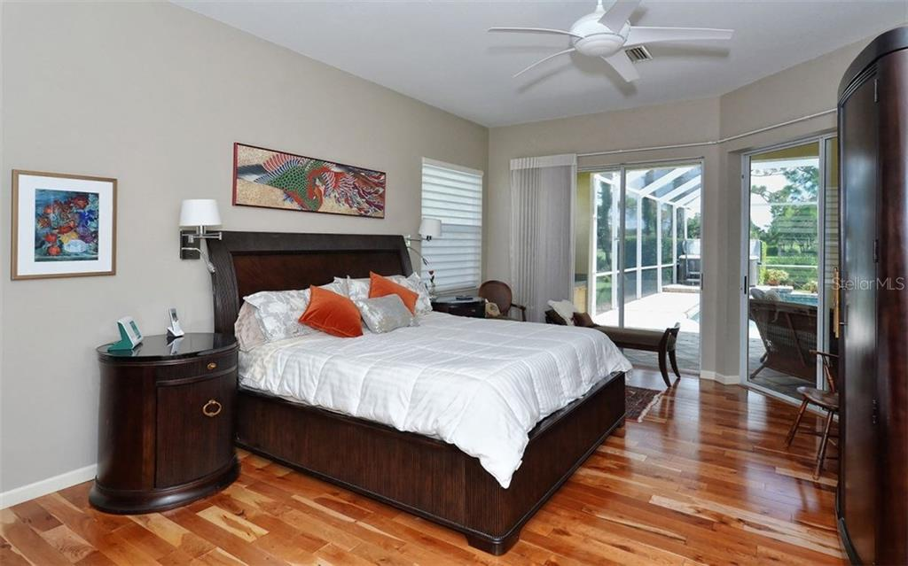 Master bedroom has 2 sets of double sliders to the lanai. - Single Family Home for sale at 8747 Grey Oaks Ave, Sarasota, FL 34238 - MLS Number is A4195019
