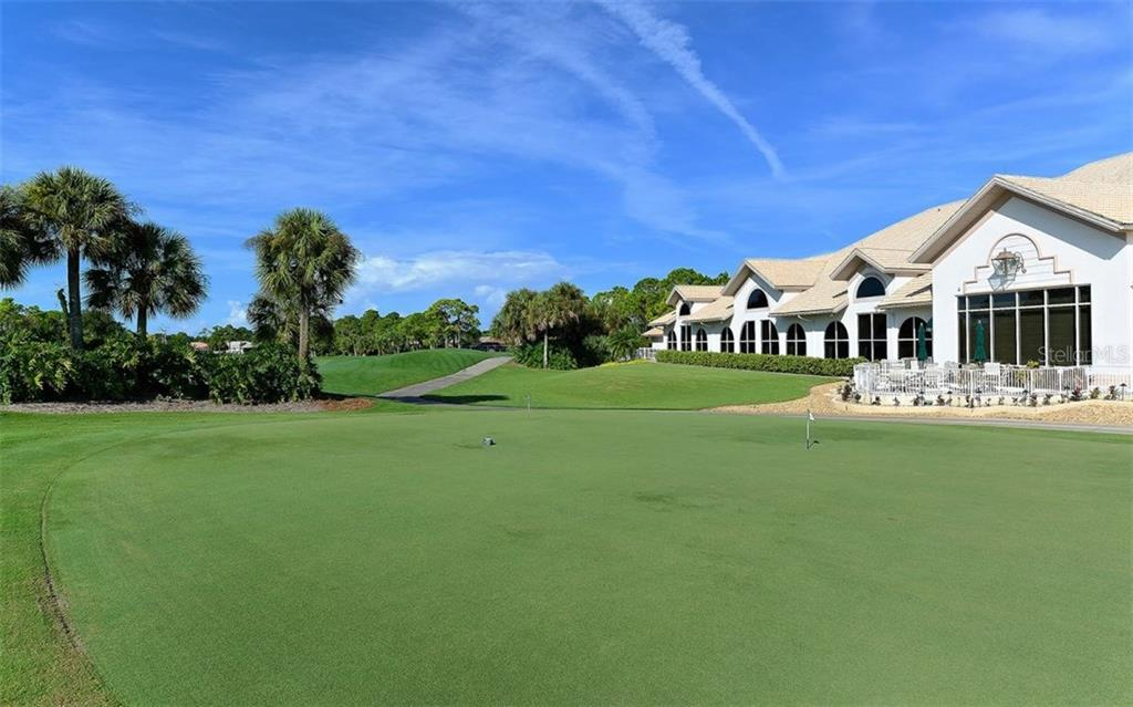 Back view of the Stoneybrook Golf & Country Club restaurant, pro shop, admin offices.  It overlooks the putting green and 18th signature hole. - Single Family Home for sale at 8747 Grey Oaks Ave, Sarasota, FL 34238 - MLS Number is A4195019