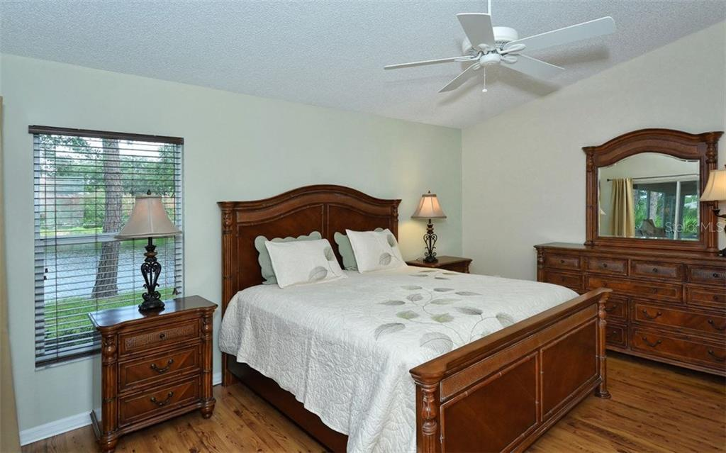 Master bedroom with water view and recently upgraded flooring.  Vaulted ceiling enhances the open feel. - Single Family Home for sale at 9571 Knightsbridge Cir, Sarasota, FL 34238 - MLS Number is A4197972