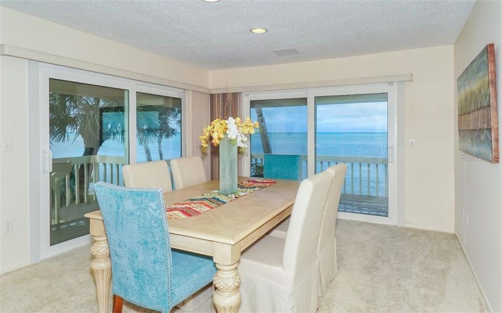 Dining room with sliders to porch and Gulf of Mexico views - Single Family Home for sale at 148 Sand Dollar Ln, Sarasota, FL 34242 - MLS Number is A4206505