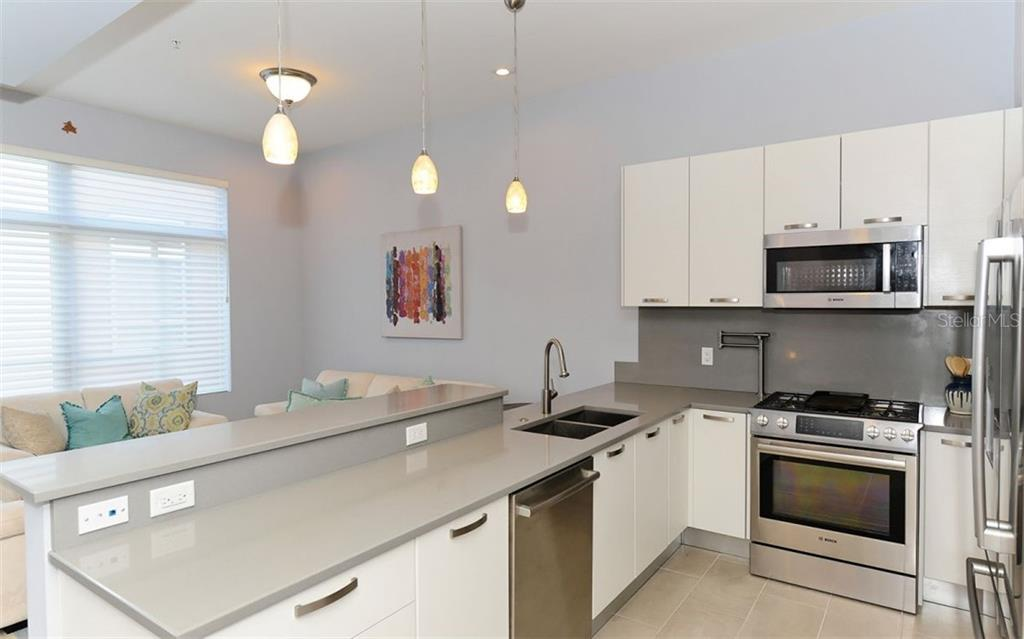 Well appointed kitchen with Bosch appliances, including a gas stove and Lube Italian Cabinets. - Townhouse for sale at 234 Cosmopolitan Ct, Sarasota, FL 34236 - MLS Number is A4207722