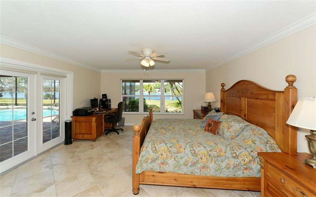 Master bedroom with French doors to the lanai and pretty water views. - Single Family Home for sale at 5122 Willow Leaf Dr, Sarasota, FL 34241 - MLS Number is A4209555
