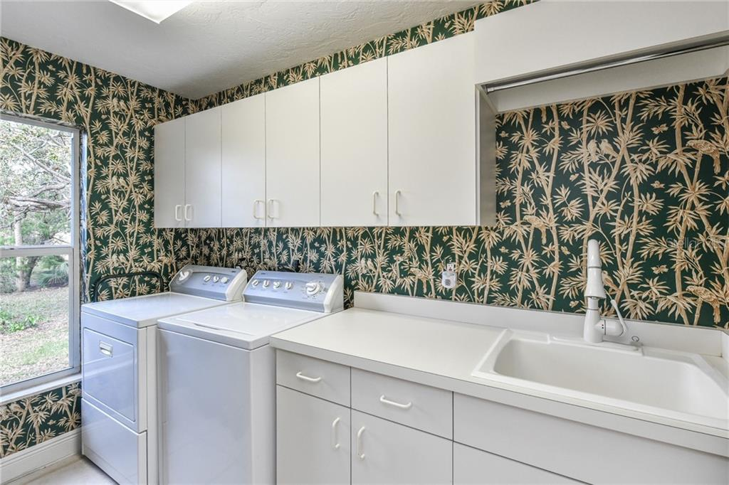 Laundry Room on the main level features both upper and lower cabinets, sink, and drying rod. - Single Family Home for sale at 5585 Siesta Estates Ct, Sarasota, FL 34242 - MLS Number is A4211109