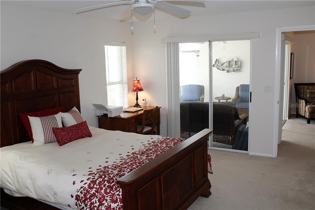 Master bedroom has sliding glass doors that lead to the lanai and screened covered porch. - Villa for sale at 5438 Kelly Dr #12, Sarasota, FL 34233 - MLS Number is A4400319