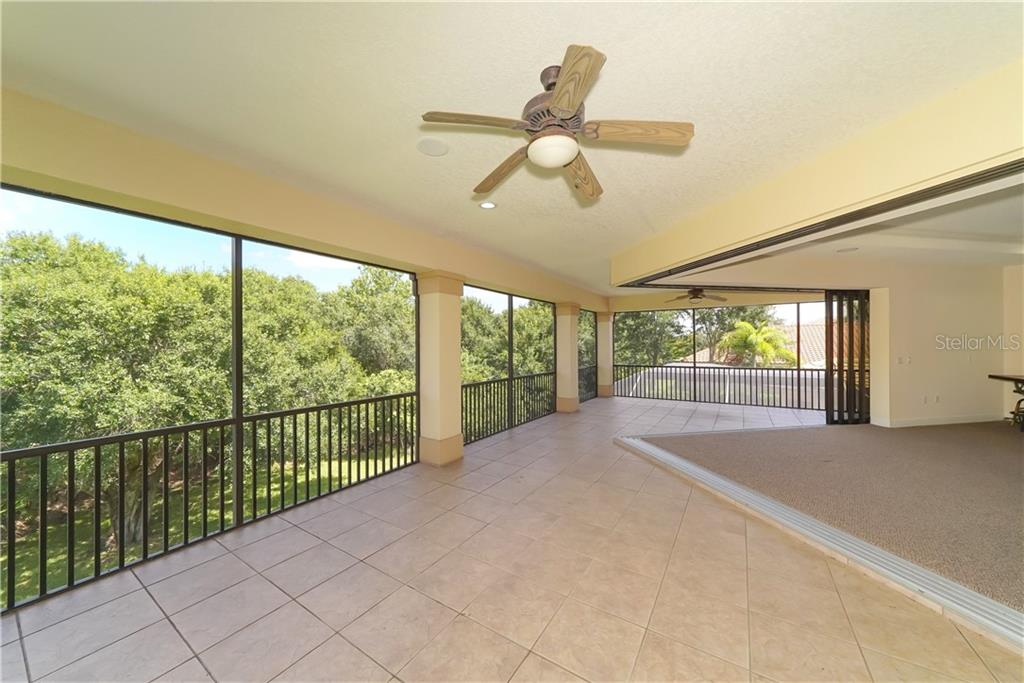 Disappearing corner and pocketing doors lead to an expansive second story lanai overlooking the back yard and preserve. - Single Family Home for sale at 13219 Palmers Creek Ter, Lakewood Ranch, FL 34202 - MLS Number is A4407857