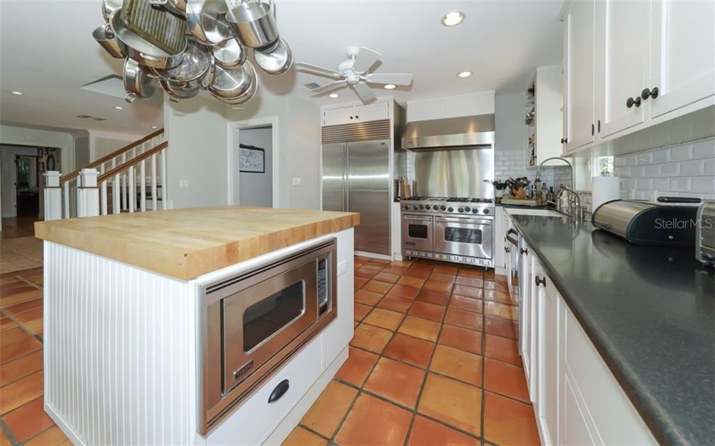 The kitchen is a masterpiece - featuring a butcher block center island with a built in wine cooler (not pictured) and a Viking microwave. - Single Family Home for sale at 138 Island Cir, Sarasota, FL 34242 - MLS Number is A4412265
