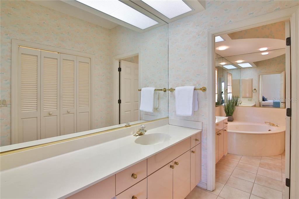 Looking into the master dressing/bathroom area, dual vanities, jetted garden tub, with separate walk-in shower and private water closet. - Villa for sale at 7686 Calle Facil, Sarasota, FL 34238 - MLS Number is A4413755