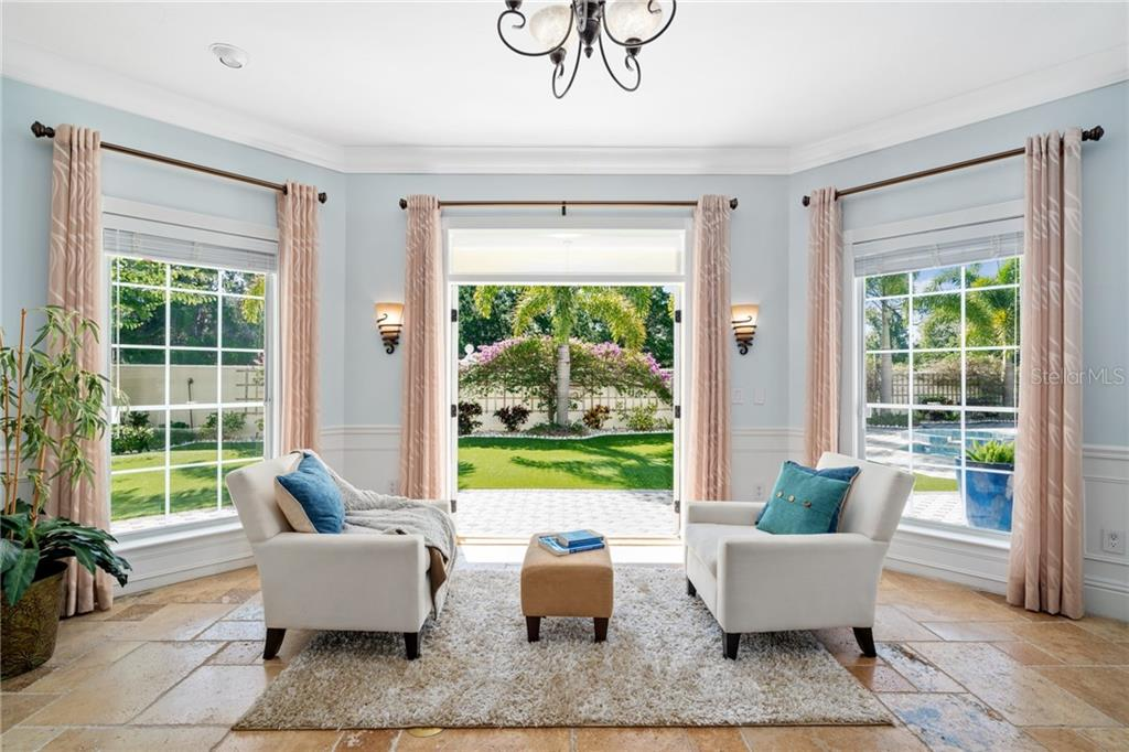 Large windows and glass-paneled French doors open to the perfectly manicured back garden and pool lanai. - Single Family Home for sale at 1654 Landings Blvd, Sarasota, FL 34231 - MLS Number is A4417765