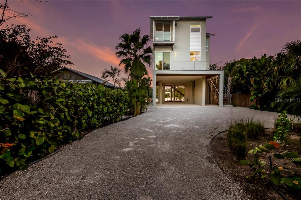 Twilight view of the front - Single Family Home for sale at 7130 Longboat Dr E, Longboat Key, FL 34228 - MLS Number is A4418105