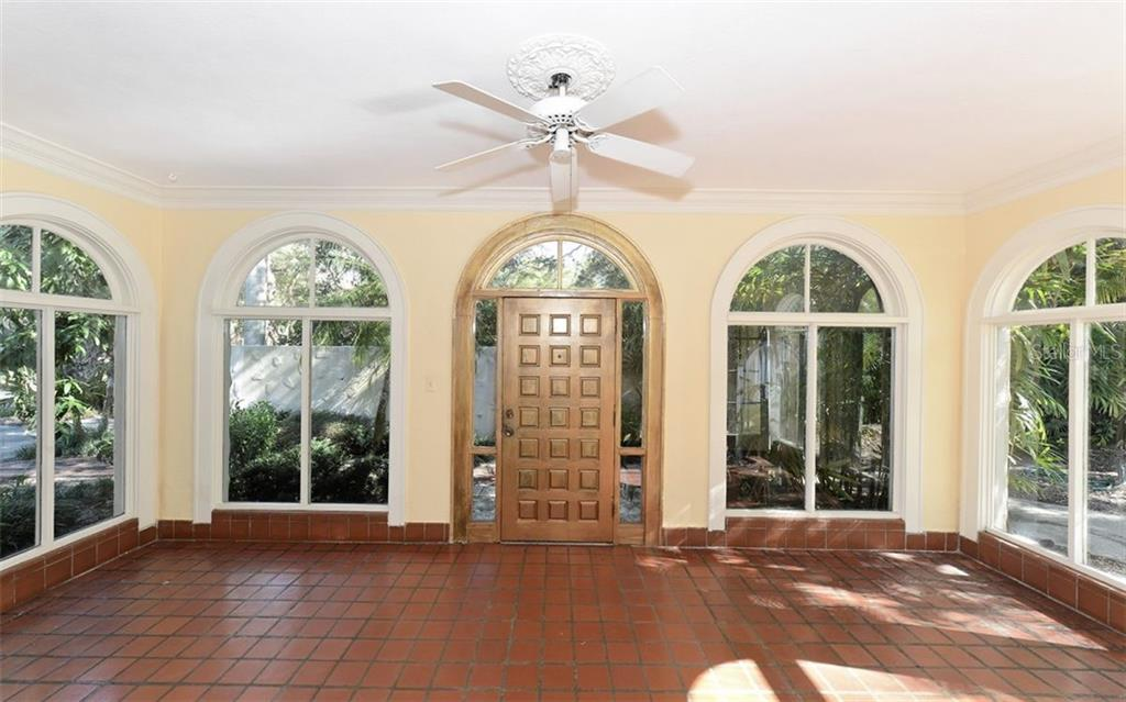 Enclosed front porch with arched windows, crown molding & a stunning solid wood door. - Single Family Home for sale at 2262 Okobee Dr, Sarasota, FL 34239 - MLS Number is A4421275