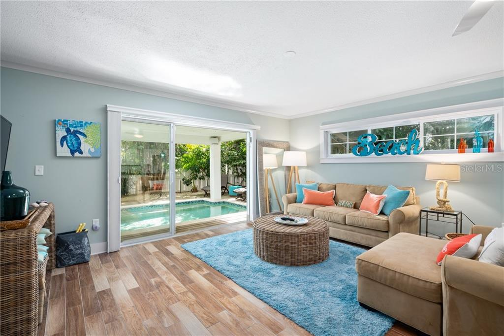 First Floor Living Room and Exit to the Backyard Pool and Spa - Single Family Home for sale at 107 Willow Ave, Anna Maria, FL 34216 - MLS Number is A4421946