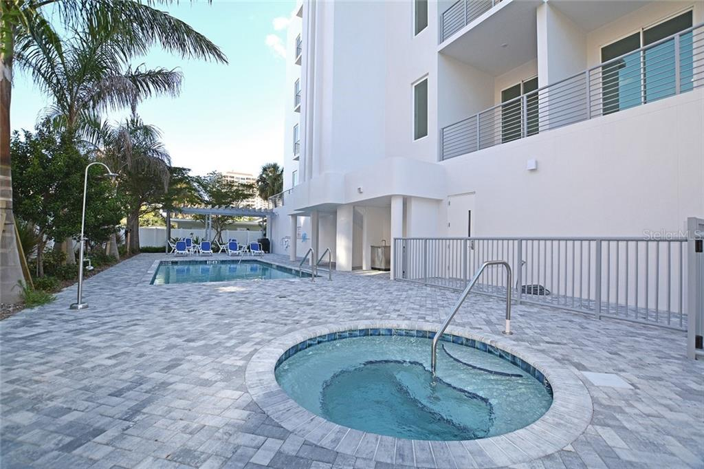 Heated saltwater pool & spa, outdoor shower, gazebo with lounge chairs and grilling station. - Condo for sale at 609 Golden Gate Pt #301, Sarasota, FL 34236 - MLS Number is A4422419