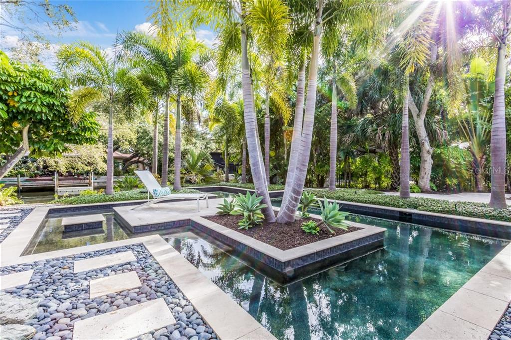 Beautiful entrance with lush tropical landscaping - Single Family Home for sale at 6957 Belgrave Dr, Sarasota, FL 34242 - MLS Number is A4423362