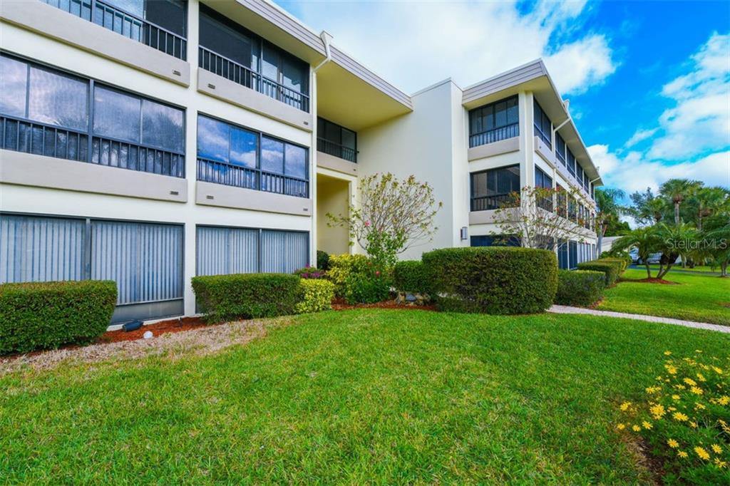 Exterior front of 225 Hourglass Way.  This midrise building is named Sunset House. - Condo for sale at 225 Hourglass Way #208, Sarasota, FL 34242 - MLS Number is A4425323