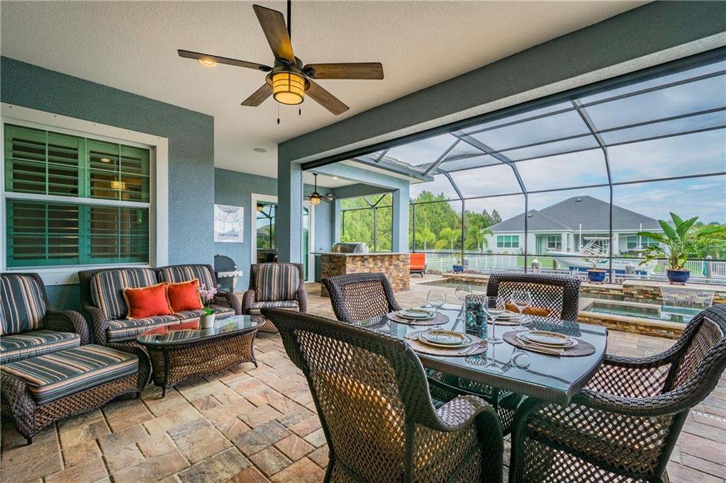 Outdoor living space off of the family room.  Space includes a roll down hurricane shade which also can be used as an enclosure of the space for entertaining. - Single Family Home for sale at 595 Fore Dr, Bradenton, FL 34208 - MLS Number is A4428657