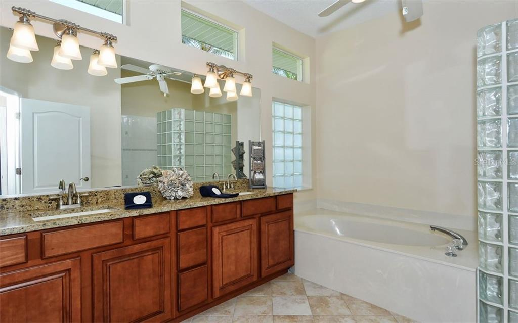 The master bath offers solid wood cabinetry, transom windows, granite countertops, dual sinks, garden tup, separate shower and water closet. - Single Family Home for sale at 1636 Liscourt Dr, Venice, FL 34292 - MLS Number is A4429524