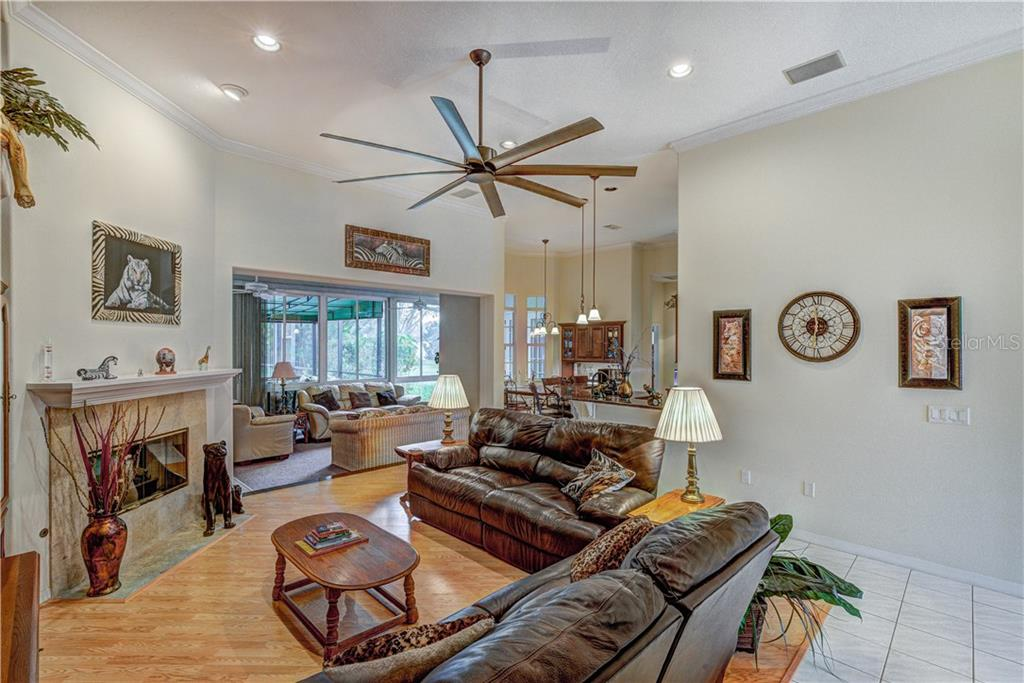Beautiful great room with electric/gas/wood fireplace that flows into florida room - Single Family Home for sale at 6321 W Glen Abbey Ln E, Bradenton, FL 34202 - MLS Number is A4429610