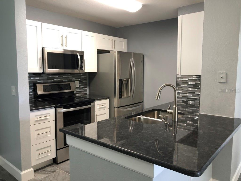Kitchen with solid cabinets, granite counter tops, tile backsplash - Condo for sale at 8923 Manor Loop #106, Lakewood Ranch, FL 34202 - MLS Number is A4434002