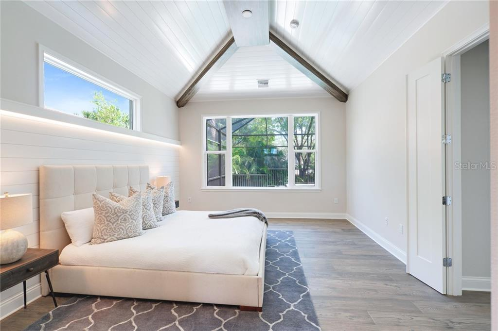 Master Bedroom with shiplap ceiling, hand painted faux wood beams, large window looking out over pool, natural lighting - Single Family Home for sale at 1555 Sandpiper Ln, Sarasota, FL 34239 - MLS Number is A4436047