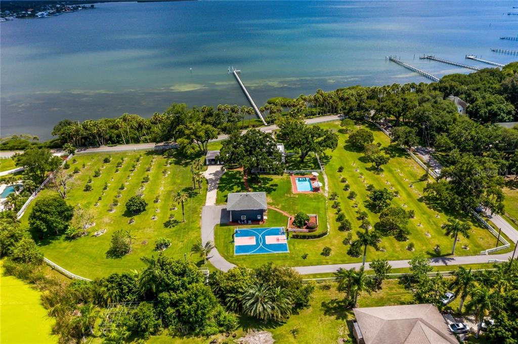 Aerial of entire estate with waterfront & dock. Private driveway leads to the guesthouse and the main house carport. - Single Family Home for sale at 590 Bayshore Dr, Terra Ceia, FL 34250 - MLS Number is A4437024
