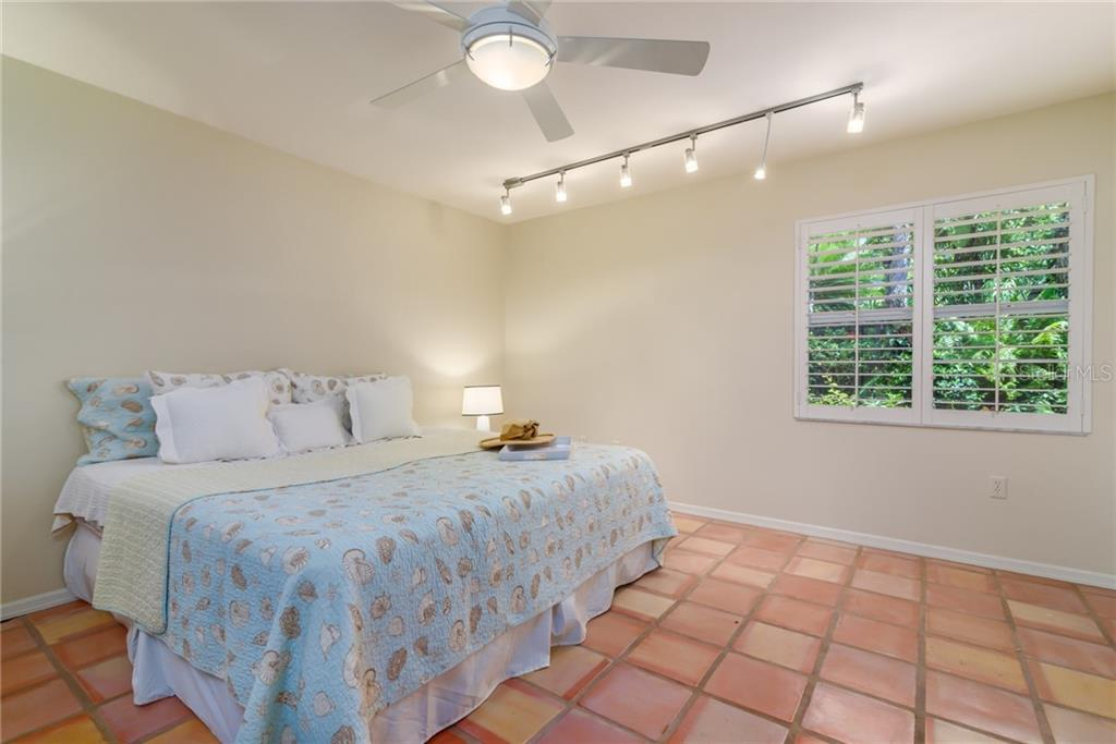 Bedroom w/ plantation shutters & view of side yard - Single Family Home for sale at 8511 Heron Lagoon Cir, Sarasota, FL 34242 - MLS Number is A4439489