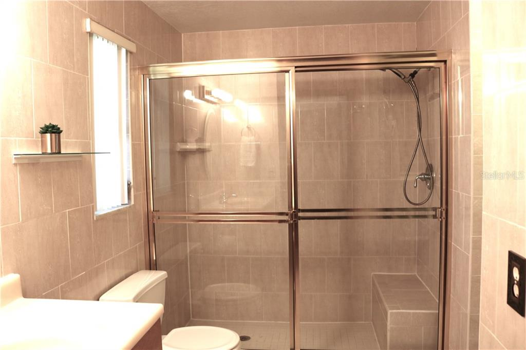 The third bathroom features a large walk in-shower with a tiled bench. - Single Family Home for sale at 2220 Pine Ter, Sarasota, FL 34231 - MLS Number is A4440562