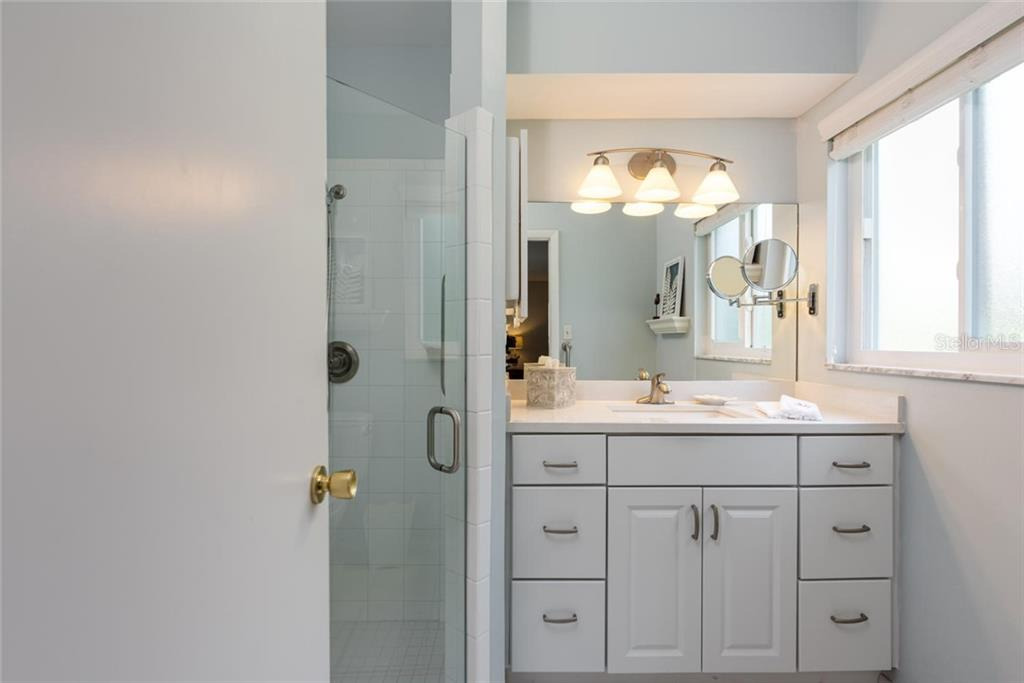 A hallway full of closets and the en-suite bathroom in the master. - Single Family Home for sale at 701 Norton St, Longboat Key, FL 34228 - MLS Number is A4440596