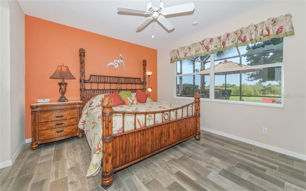 Master bedroom with wood look tile and huge window to take in views of the gorgeous lake and preserve beyond. - Single Family Home for sale at 114 Padova Way #52, North Venice, FL 34275 - MLS Number is A4442496