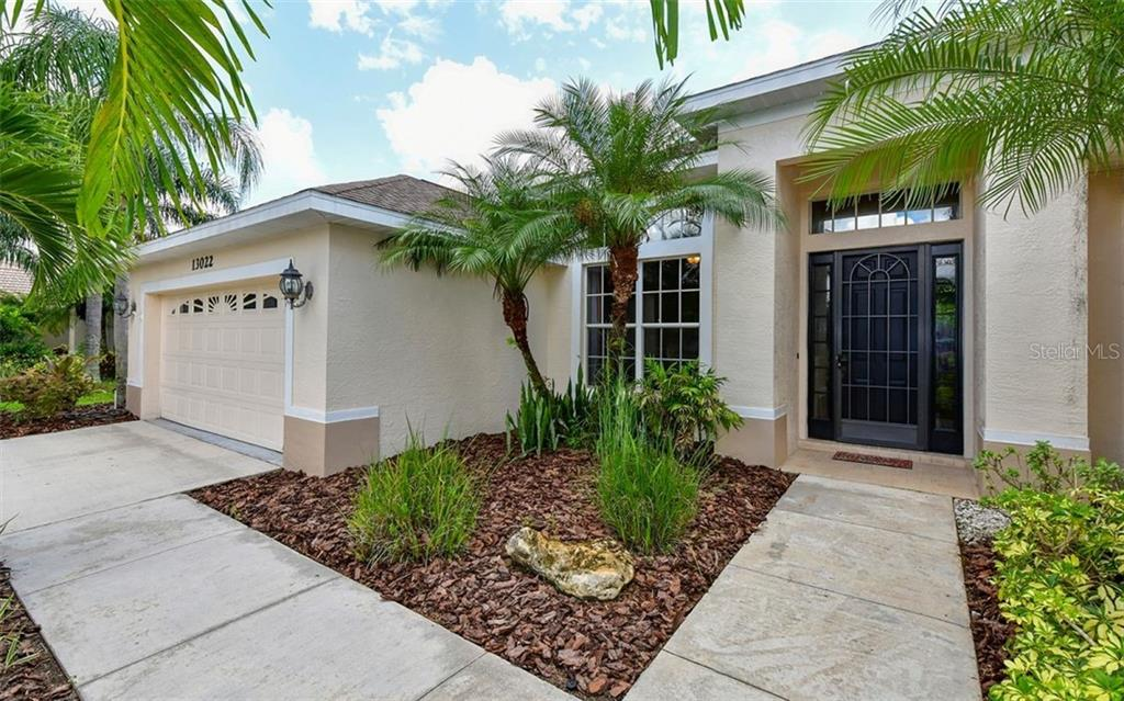 Specialty palms & mature landscaping surround the property - Single Family Home for sale at 13022 Peregrin Cir, Bradenton, FL 34212 - MLS Number is A4444939
