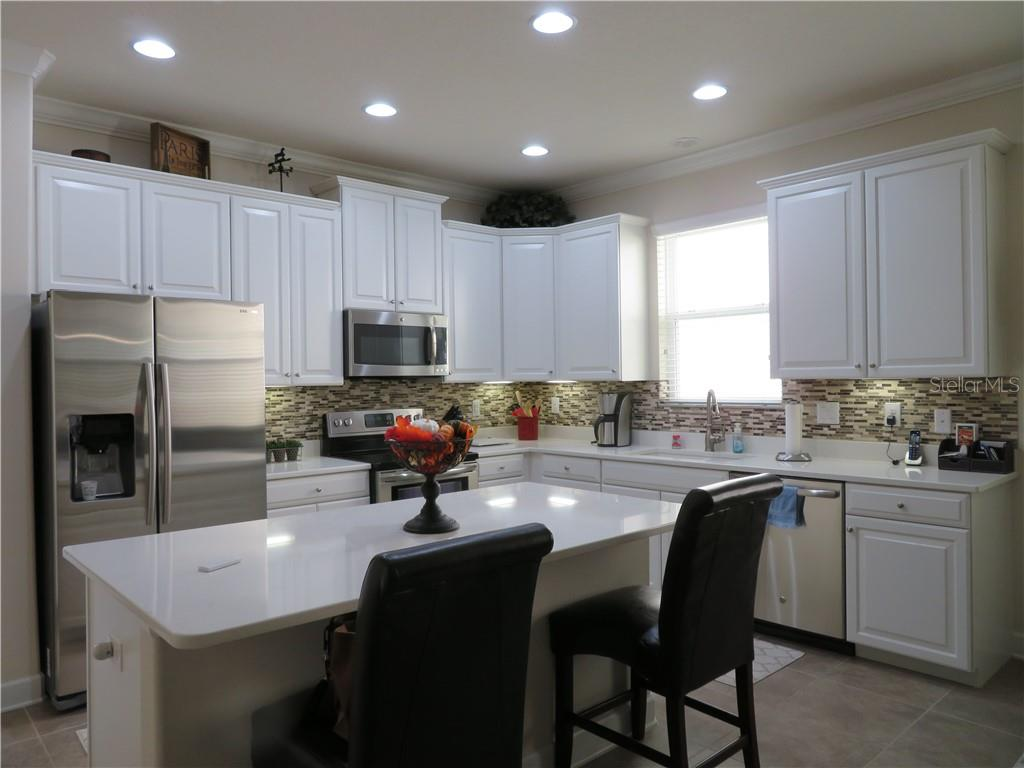 Elegant kitchen with quartz counters, stainless appliances and tile backsplash . Large island for entertaining - Single Family Home for sale at 5727 Arbor Wood Ct, Bradenton, FL 34203 - MLS Number is A4448047