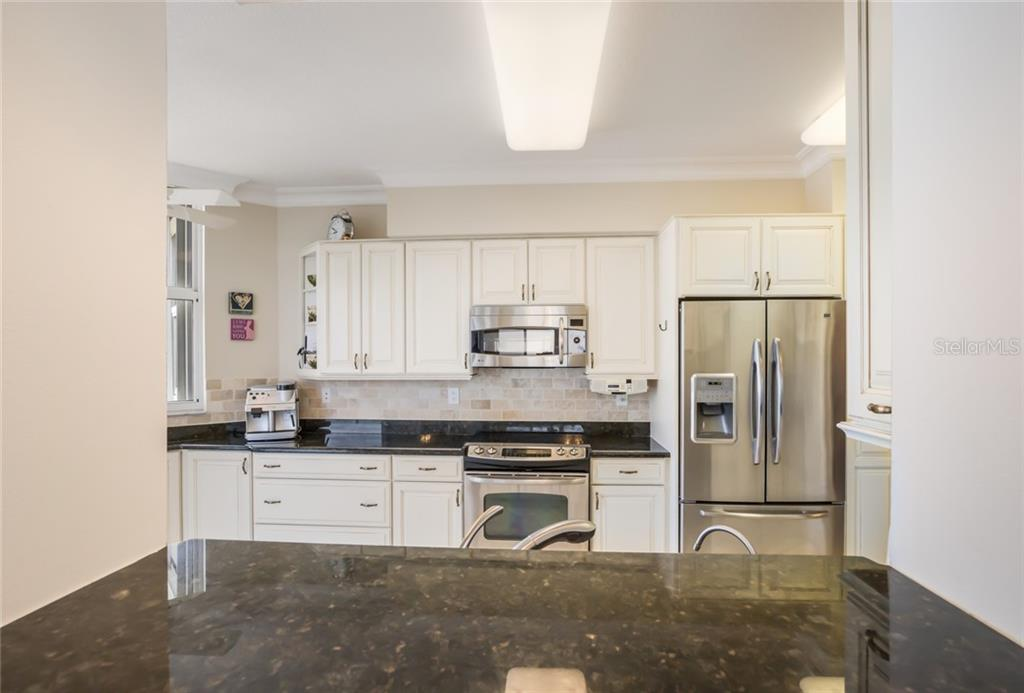 Fully updated kitchen with open bar seating and pass through. - Condo for sale at 1800 Benjamin Franklin Dr #b506, Sarasota, FL 34236 - MLS Number is A4451047