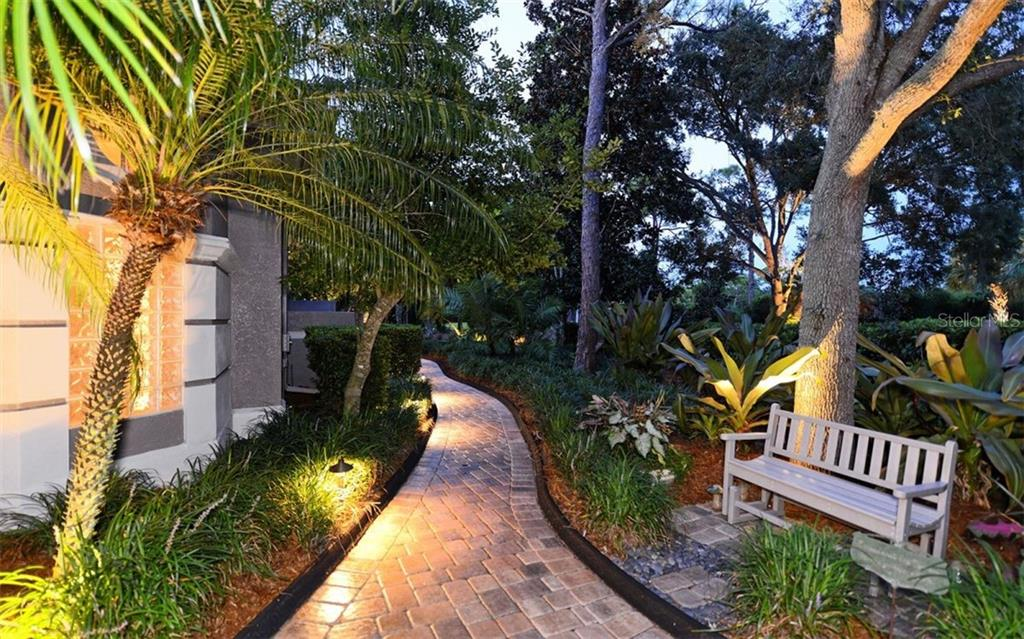 Landscape lighting along the paver pathways. - Single Family Home for sale at 586 N Macewen Dr, Osprey, FL 34229 - MLS Number is A4451482