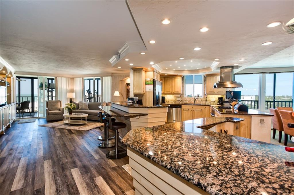 A view of the living area with gulf views and gourmet kitchen with breakfast counter and wine bar - Condo for sale at 5880 Midnight Pass Rd #911, Sarasota, FL 34242 - MLS Number is A4462559