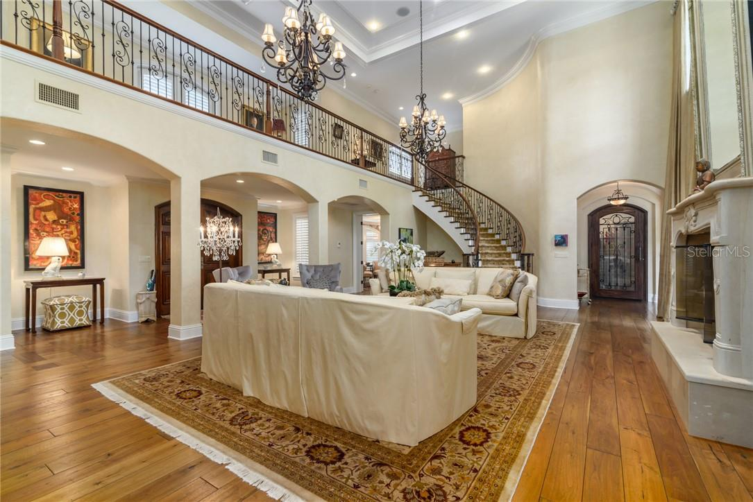 A Grand Foyer blossoms into a two story living room with crackling fireplace beckoning, and a winding staircase leads you to the 2nd floor spacious library and two bedrooms ensuite. - Single Family Home for sale at 1807 Oleander St, Sarasota, FL 34239 - MLS Number is A4475067