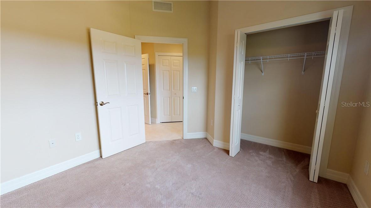 Second bedroom into guest hallway - Condo for sale at 5591 Cannes Cir #506, Sarasota, FL 34231 - MLS Number is A4484243